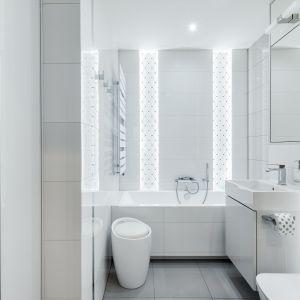 Charakter głównej łazienki buduje dekoracyjna ściana za wanną z podświetloną mozaiką Tubądzin Abisso White.c Projekt: Justyna Mojżyk, poliFORMA. Fot. Monika Filipiuk-Obałek