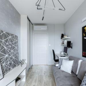 Pokój syna wpisuje się w charakter całego mieszkania. Wzdłuż ściany pokrytej srebrną strukturą ciągnie się nieregularna zabudowa z metalizowaną krawędzią. Projekt: Justyna Mojżyk, poliFORMA. Fot. Monika Filipiuk-Obałek