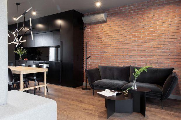 Pozornie surowe wnętrze łagodzą miękkie formy kanap, a ciemną kolorystykę przełamują naturalne elementy drewna i cegły. Takie mieszkanie przygotowała dla inwestora pracownia Kreacja Przestrzeni.