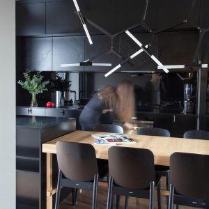 """W tym projekcie zdecydowanie rządzą proste formy, dlatego architekci zdecydowali się na """"ukryte"""" drzwi, metalowe, geometryczne elementy połączone z matowymi frontami zabudowy czy krzesła wykonane ze sklejki. Projekt: Kreacja Przestrzeni. Fot. Hubert de Jakusz-Gostomski"""