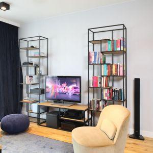 Proste, metalowe półki w małym salonie urządzonym nowocześnie sprawdził się znakomicie. Projekt: Maciejka Peszyńska-Drews. Fot. Bartosz Jarosz