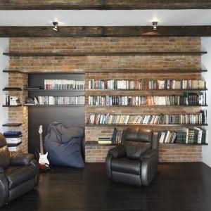 Książki w salonie zostały wyeksponowane na tle ceglanej ściany.   Drewniane półki wpisują się w tą aranżację idealnie. Projekt: Iza Mildner. Fot. Bartosz Jarosz