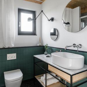 Okrągłe lustro nad umywalką w łazience. Projekt: Raca Architekci. Fot. Fotomohito