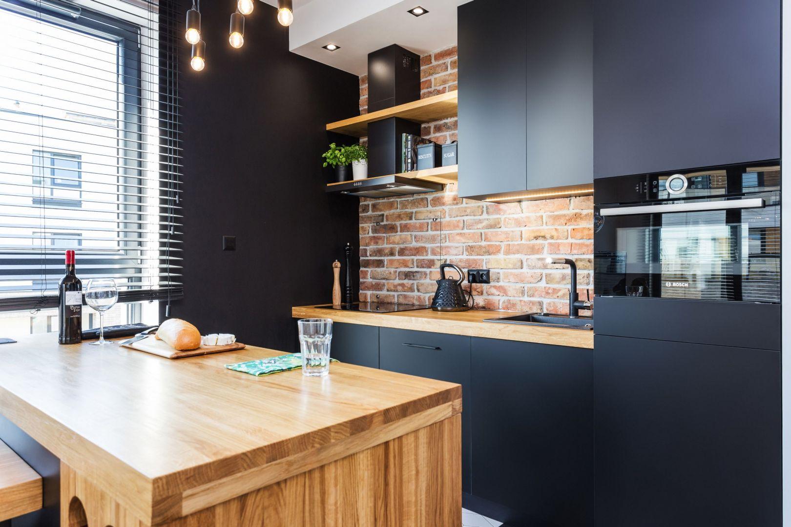 Małą kuchnię urządzono w czerni. Projekt Deer Design