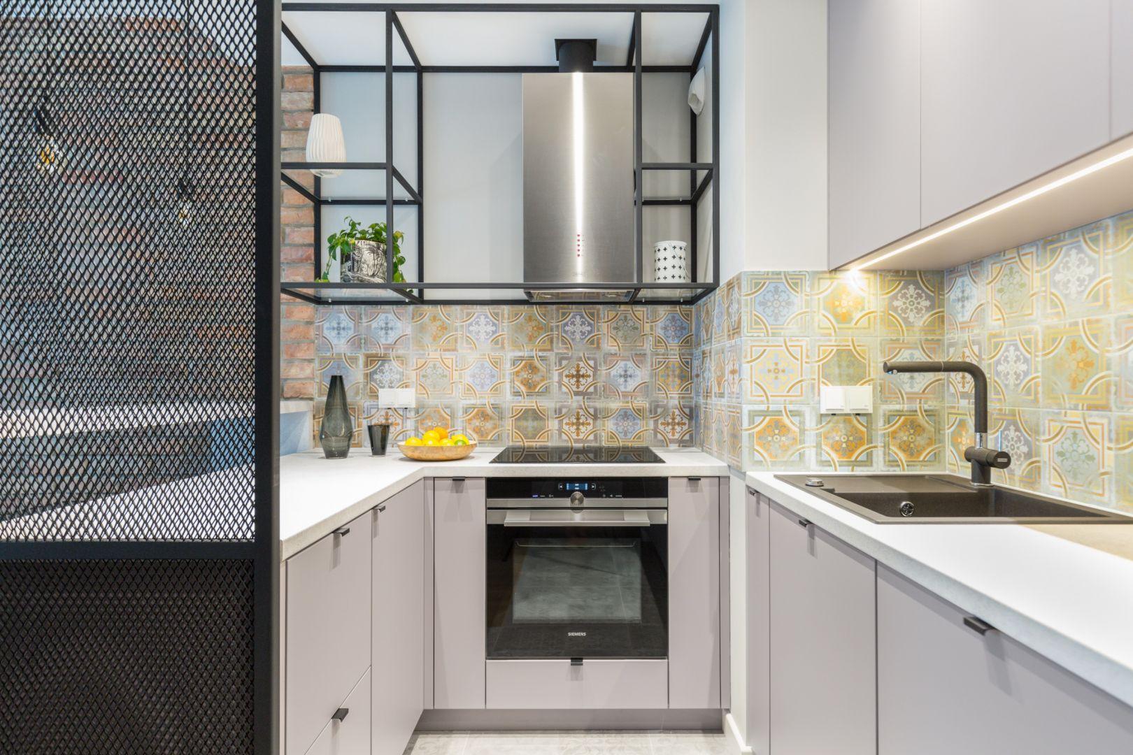 W małej kuchni uwagę przyciągają dekoracyjne kafle nad blatem. Projekt Decoroom. Fot. Pion Poziom