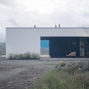 Minimalistyczną stylistykę domu podkreśla dwukolorowa elewacja skomponowana z białego tynku oraz wysokiej jakości drewna elewacyjnego. Projekt: pracownia HomeKONCEPT