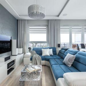 W salonie dominują jasne, stonowane kolory. Jedynym mocnym akcentem jest duży, turkusowo-biały narożnik. Projekt: Justyna Mojżyk, poliFORMA. Fot. Monika Filipiuk-Obałek