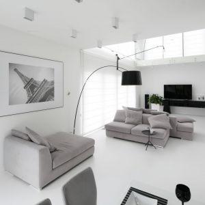 Salon urządzony jest w białym kolorze. Białe są ściany oraz podłoga. Mocnym elementem w jasnym wnętrzu jest czarna lampa. Projekt: Maria Biegańska, Ewelina Pik. Fot. Bartosz Jarosz