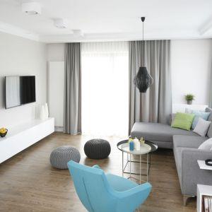 W salonie dominuje kolor biały i szary, który ociepla drewniana podłoga i ożywa turkusowy fotel. Projekt: Małgorzata Galewska. Fot. Bartosz Jarosz
