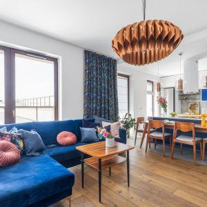 Nowoczesny kolorowy salon z niebieską sofą i otwartą kuchnią. Projekt: Joanna Rej. Fot. Marta Behling/Pion Poziom