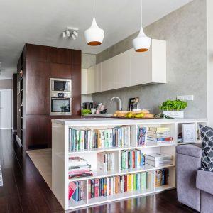Miejsce na książki w salonie - na małym metrażu dobrze sprawdzi się taka niska półka, która jednoczesnie jest półwyspem kuchennym. Projekt: Decoroom. Fot. Pion Poziom