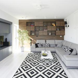 Ścianę za kanapą zdobią drewniane półki. Projekt Ewelina Pik, Maria Biegańska. Fot. Bartosz Jarosz