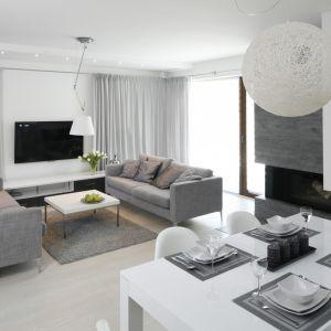 Oświetlenia w białym kolorze doskonale pasuje do szarej kolorystki salonu. Projekt: Katarzyna Stanek-Szadujko, Łukasz Szadujko. Fot. Bartosz Jarosz