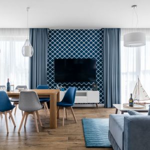 Niebieska dekoracyjna tapeta na ścianie z telewizorem i dobrze pasujące do niej deski na podłodze. Projekt: Studio Projekt. Fot. Fotomohito
