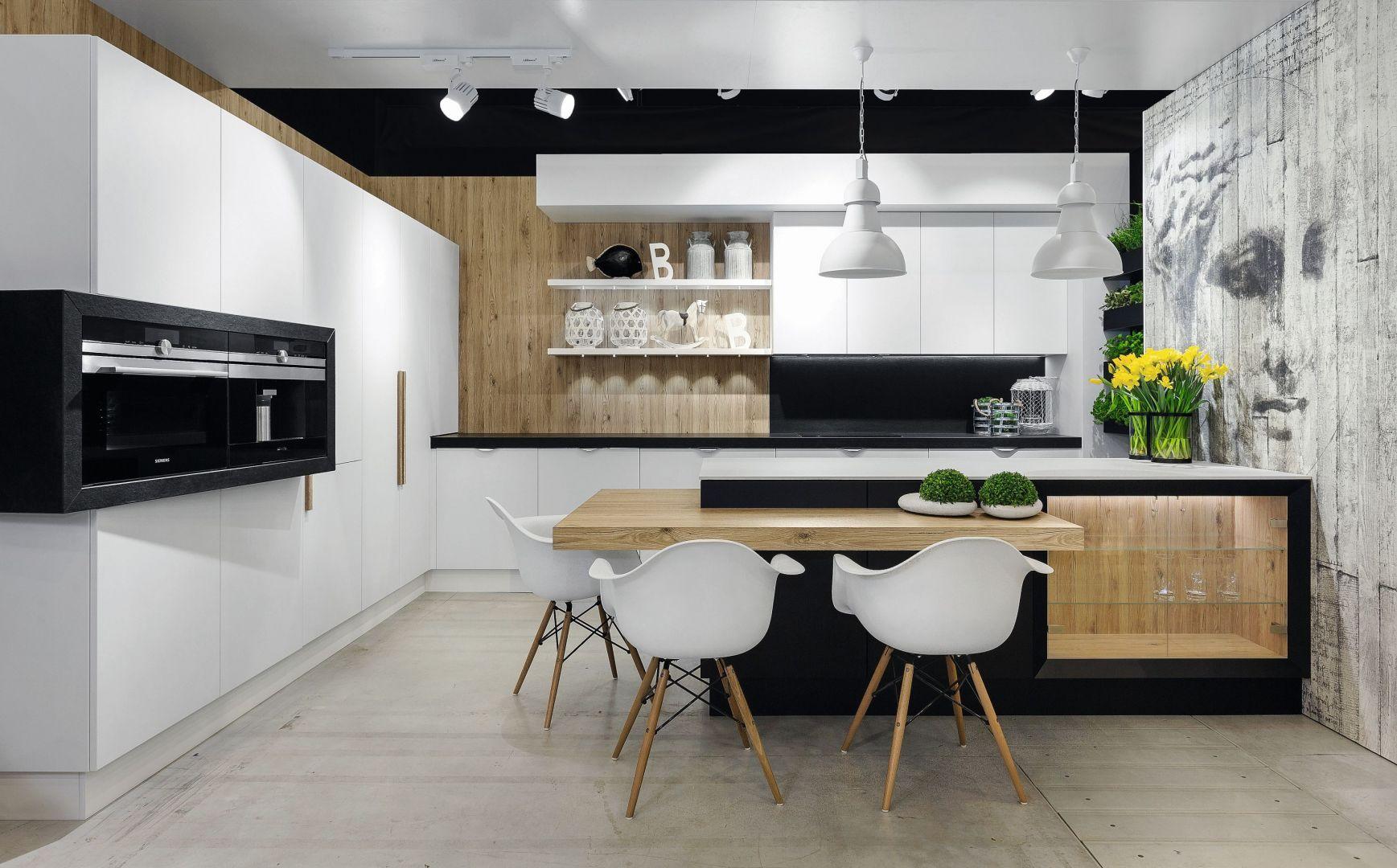 Drewno stanowi znaczące tło dla białej zabudowy kuchennej. Projekt Vigo Meble. Fot. Artur Krupa