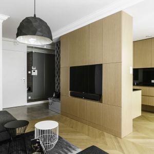 Telewizor został umieszczony na ścianie oddzielającej kuchnię od strefy wypoczynkowej. Została ona wykończona drewnem. Projekt: Anna Maria Sokołowska. Fot. Fotomohito