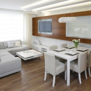 Ścianę za kanapą zdobi drewniany panel, które w duecie z bielą wygląda super. Projekt: Małgorzata Mazur.  Fot. Bartosz Jarosz
