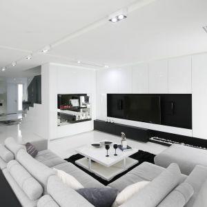 Ścianę, na które znajduje się telewizor wykończono bardzo elegancko i praktycznie. Białe fronty skrywają bowiem pojemne szafki. Projekt: Małgorzata Muc, Joanna Scott. Fot. Bartosz Jarosz