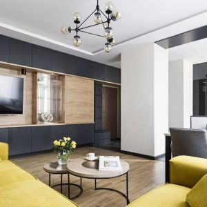 Ścianę, na której znajduje się telewizorem zdobią panele z jasnego, dębowego drewna oraz szafki, których fronty wykończono ciemnym, szarym kolorem. Projekt: MMA Pracownia Architektury. Fot. Rafał Chojnacki