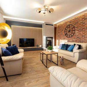 Ścianę za telewizorem pięknie zdobią drewniane panele w jasnym kolorze. W duecie z cegłą prezentują się super. Projekt: Anna Kamińska, Fuxja Studio Projektowe. Fot. Alla Boroń