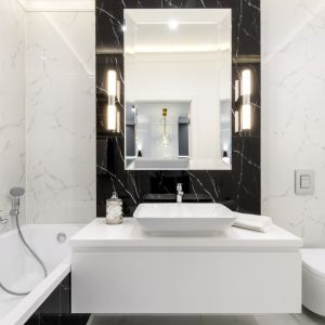 Elegancka łazienka wykończona płytkami z rysunkiem marmuru w nieśmiertelnej bieli i czerni. Projekt: Moovin Interiors