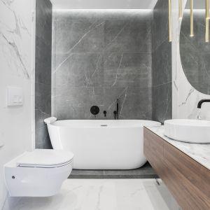 Nawet w mniejszej łazience możemy wstawić wannę wolnostojącą - ważne aby dobrze zagodpodarować każdą dostępną przestrzeń. Projekt: Moovin Interiors