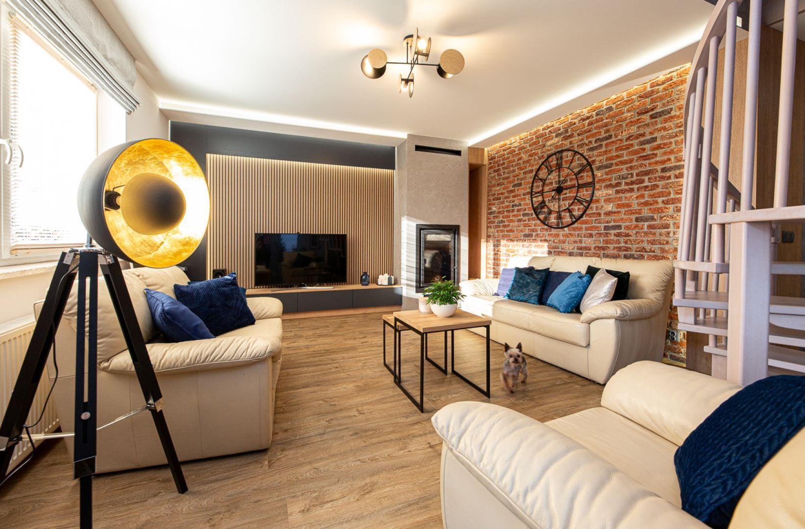 Podłoga i ściana w przytulnym salonie. Na ścianie cegła i drewno, na podłodze - piękne deski. Projekt: Anna Kamińska, Fuxja Studio Projektowe. Fot. Alla Boroń