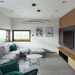 Podłoga i ściana w salonie. Na podłodze szare płytki podłogowe, na ścianie - drewniane lamele. Projekt: Estera i Robert Sosnowscy, Studio Projekt. Fot. Studio MM