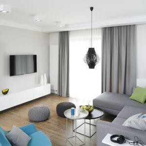 Stolik i kanapa w salonie. Dwa stoliki w skandynawskim minimalistycznym stylu pasują do szarej kanapy. Projekt: Małgorzata Galewska. Fot. Bartosz Jarosz