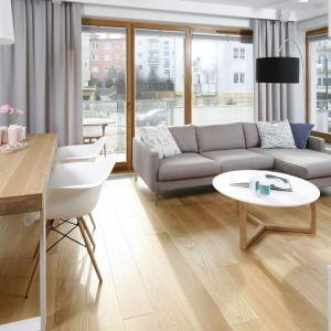 Stolik i kanapa w salonie. Biały stolik kawowy na drewnianych nóżkach świetnie się prezentuje w duecie z beżową sofą. Projekt: Przemek Kuśmierek. Fot. Bartosz Jarosz