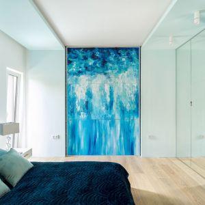 Master bedroom czyli sypialnia państwa domu jest beżowo-niebieska. Główny i właściwie jedyny mebel we wnętrzu to łóżko o asymetrycznym pikowanym wezgłowiu. Projekt Trędowska Design. Fot Michał Bachulski