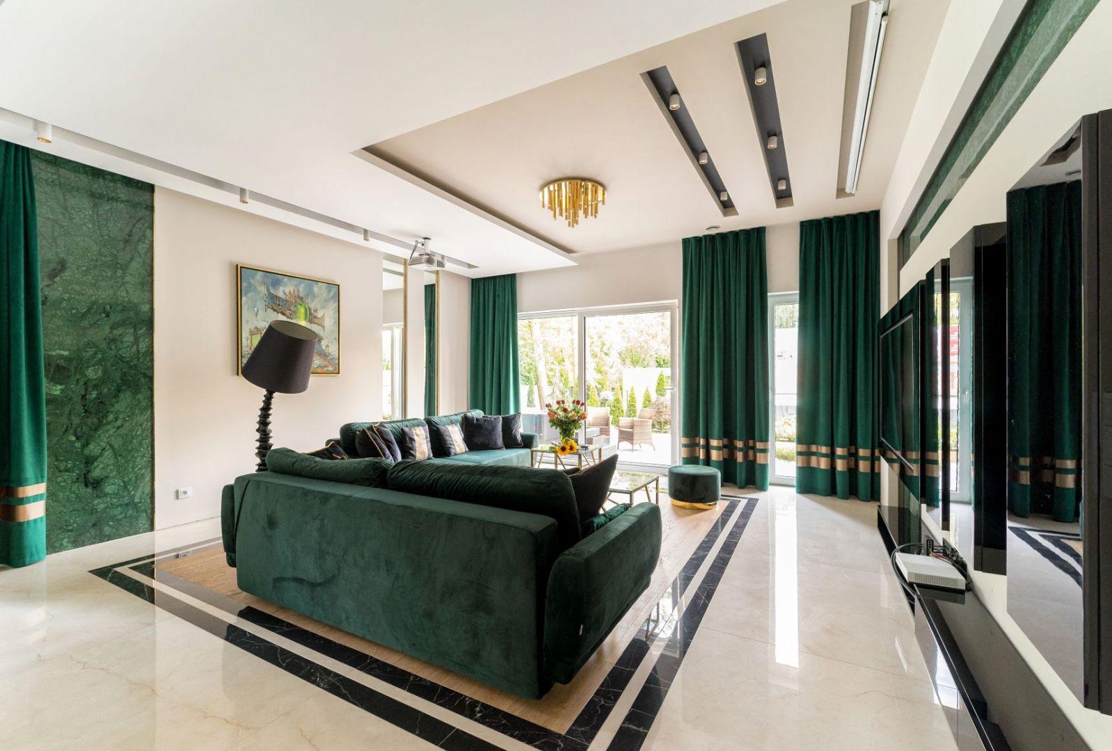 Wygodne, klasyczne sofy tapicerowane ciemno turkusowym welurem nadają ton kolorystyce wnętrza i zapraszają do relaksu. Projekt Trędowska Design. Fot Michał Bachulski