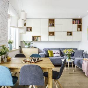 W małym salonie połączony z jadalnią zaplanowano sporo miejsca na przechowywanie nad kanapą. Projekt: Joanna Morkowska-Saj. Fot. FotoMohito