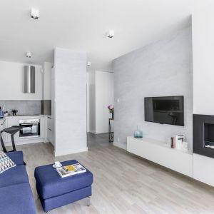 Pomysł na ściany w małym salonie - biała farba i jasna tapeta w chłodnym kolorze powiększają optycznie pomieszczenie. Projekt: Decoroom. Fot. Pion Poziom