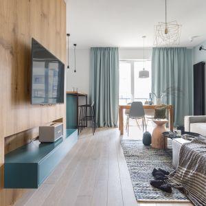 Pomysł na ściany w małym salonie. Odcienie niebieskiego to dobry pomysł do małego wnętrza. Naturalne drewno może je ocieplić. Projekt: Alina Fabirowska. Fot. Pion Poziom