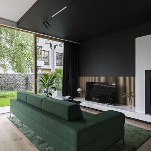 Nowoczesny salon urządzono w ciemnych kolorach. Duże przeszklenia rozświetlają wnętrze. Projekt KAEL Architekci foto Rafał Chojnacki