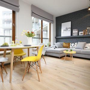 Mały okrągły stół i plastikowe krzesła tworzą jadalnię w salonie w stylu skandynawskim. Projekt: Ola Kołodziej, Ula Szmyt. Fot. Bartosz Jarosz