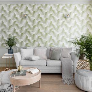 Ścianę za kanapą zdobi tapeta z modnym motywem liści. Projekt Finchstudio
