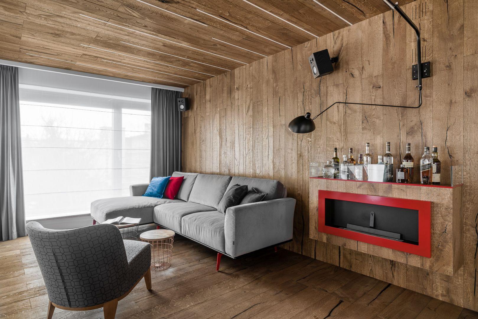 Ścianę za kanapą, podobnie jak podłogę i sufit, zdobi drewno. Projekt Anna Maria Sokołowska. Fot. Fotomohito