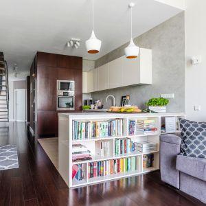 Salon od kuchni oddziela regał na książki. Projekt Decoroom. Fot. Pion Poziom