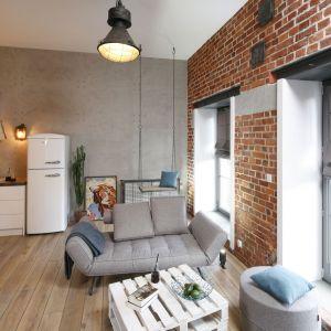 W loftowej aranżacji kuchnia stanowi tło dla aranżacji salonu. Projekt Nowa Papiernia. fot. Bartosz Jarosz