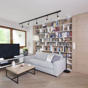 Półki na książki w salonie poprowadzono na całą ścianę. Projekt Katarzyna Kiełek Fot. Bartosz Jarosz