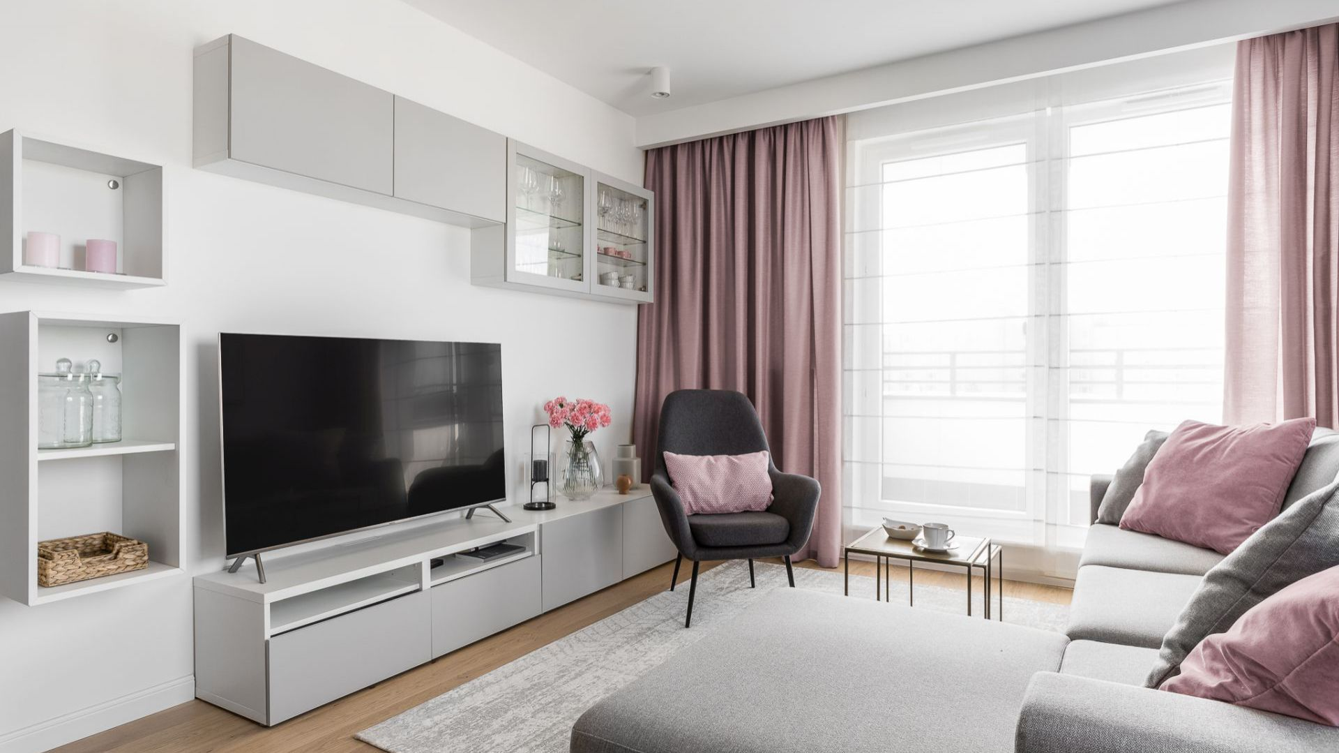 Nowoczesny jasny salon w bloku. Biała zabudowa na ścianie telewizyjnej, prosta szara sofa i kolor w dodatkach. Projekt: Barbara Wojsz. Fot. Fotomohito