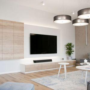 Drewniana szafka pod telewizor tworzy jedną całość z półkami wiszącymi na ścianie. Projekt: arch. Ewelina Mikulska-Ignaczak, Mikulska Studio. Fot. Jakub Ignaczak, K1M1