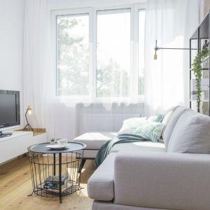 W niedużym, nowoczesnym salonie świetnie wygląda biała szafka na różkach z elementami drewna. Projekt i zdjęcia: Katarzyna Kiełek, Agnieszka Komorowska-Różycka