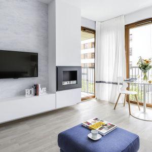 Biała, powieszana szafka bez uchwytów idealnie pasuje do nowoczesnego salonu. Projekt i zdjęcia: Decoroom