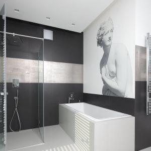 Ściany w łazience wykończono płytki w dwóch kolorach. Aranżacji charakteru dodaje oryginalna grafika. Projekt: Agnieszka Hajdas-Obajtek. Fot. Bartosz Jarosz