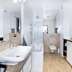 Ściany w niewielkiej łazience wykończono białą farbą oraz płytami doskonale imitującymi drewno. Projekt i zdjęcia: Joanna Nawrocka