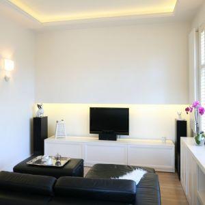 Duża, szafka pod telewizor w białym kolorze doskonale wtapia się w aranżację salonu. Projekt: Małgorzata Galewska. Fot. Bartosz Jarosz