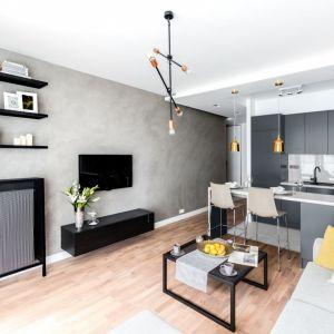 Na ścianie wykończonej betonowym tynkiem świetnie wygląda czarna, podwieszana szafka pod telewizor. Projekt i zdjęcia: Decoroom